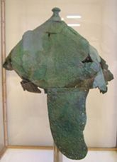 """Knossos helmet, 1450 B.C. Similar conical helmet made of bronze has been found in one of the as called """"warriors' graves"""" near Knossos. This specimen has two large cheek guards probably stitched or riveted to the helmet and an upper pierced knot to hold a crest. Small holes all around the cheek guards and helmet lower edge were used for attachment of an internal padding more likely made of linen, felt or leather."""