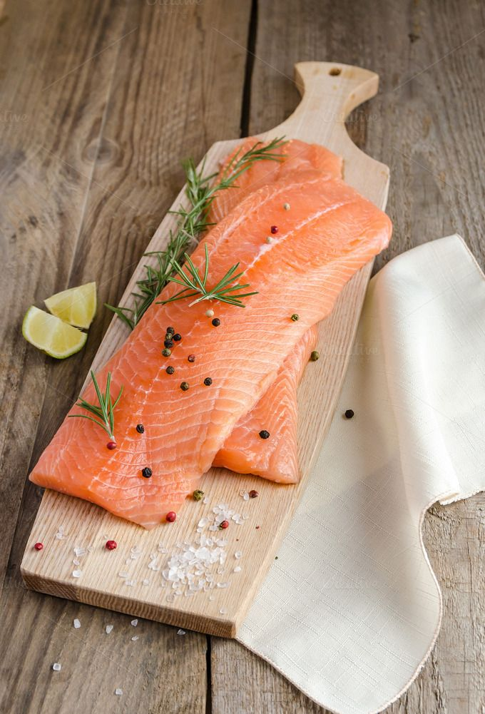 Raw salmon steaks on the wooden boar by Phototasty on @creativemarket