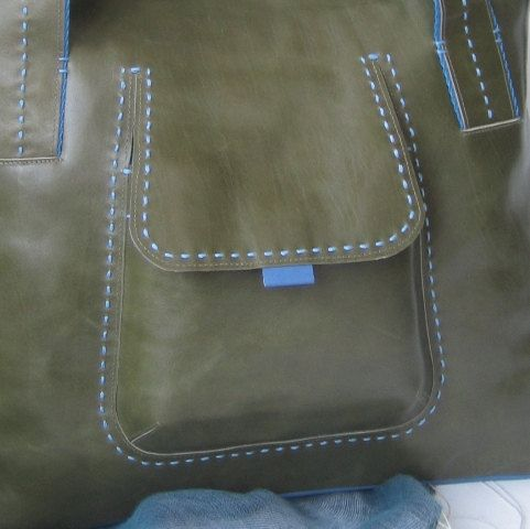 This comfortable and stylish handbag is suitable for every day. It has medium double handles and attractive relief pocket in front wich closes with magnetic button. Handmade from Italian leather in a classic combination of spanish olive green color and marine blue. There is one main interior compartment, closed with a zipper at the top. The interior is made from quilted polyester lining and contains one zipper pocket and two open pockets for a mobile phone and other essentials. Approximate…