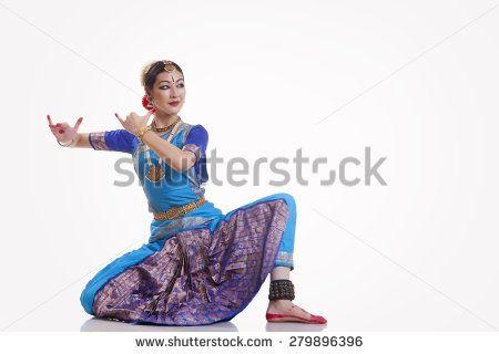 Full length of female dancer performing Bharatanatyam against white background