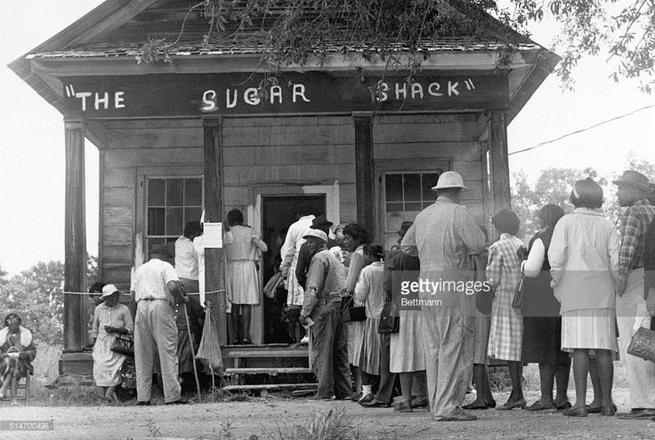 African American voters, able to vote for the first time in rural Wilcox County, Alabama, line up in front of a polling station at The Sugar Shack, a local general store. After the passage of the federal voting rights law in 1965, there were almost twice as many black voters than whites. | Location: Peachtree, Alabama, USA.