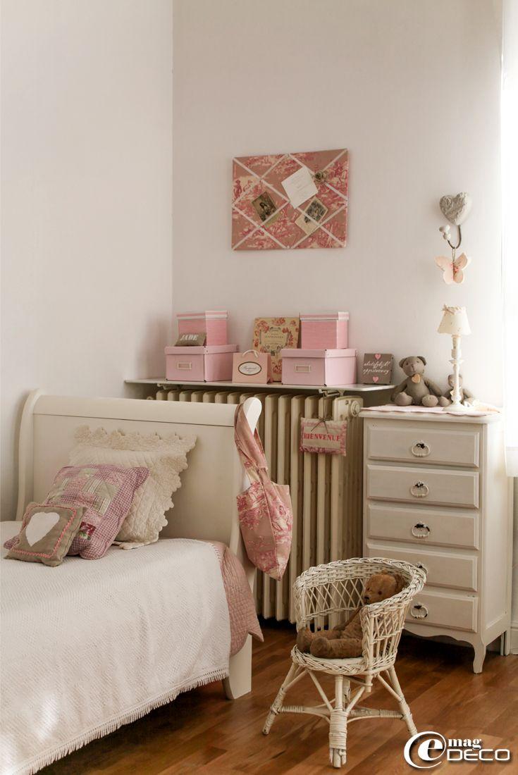 Dans une chambre d'enfant, un boutis rose 'Côté Table' et une tablette au-dessus d'un radiateur servant à exposer une collection de boîtes d...