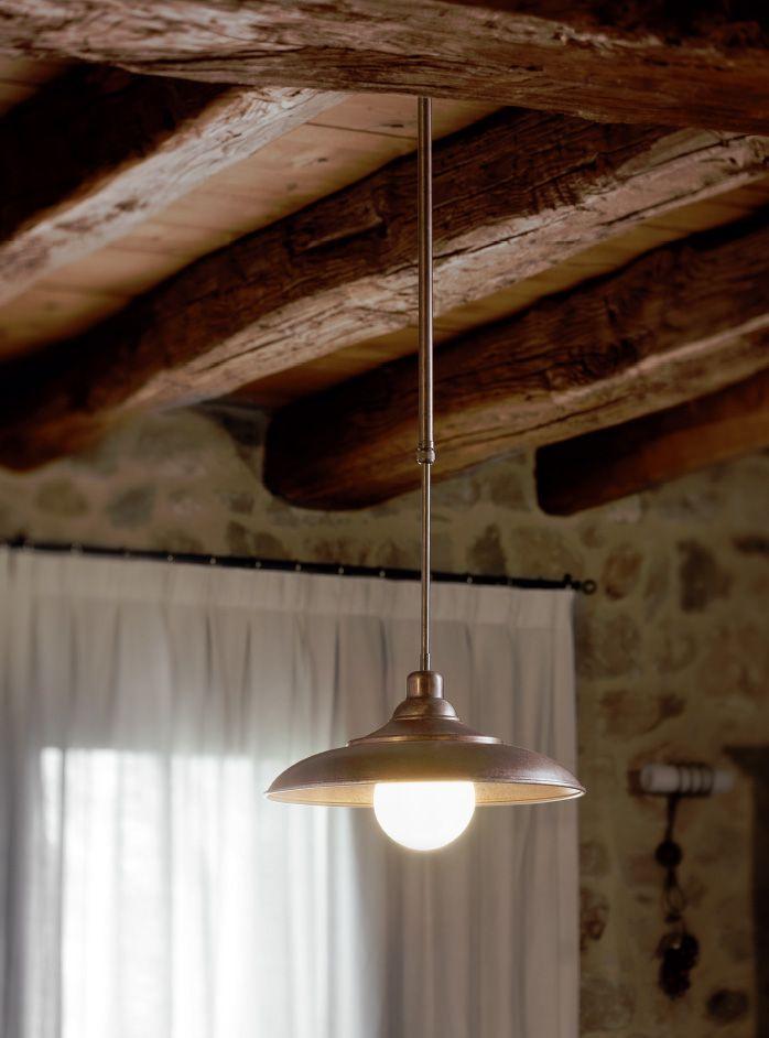 """Tosca è una serie di lampade a sospensione regolabili in altezza al momento dell'installazione, con asta in ottone e riflettore in rame anticato, disponibili nelle versioni con riflettore bombato o """"pagoda""""."""