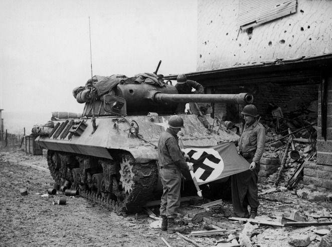 """Tankistas"" of Patton's Third Army roll up a Nazi flag they have captured after the fall of Bitburg, Germany, Feb 1945."