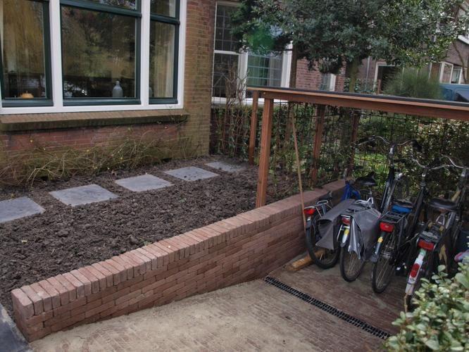 Geen achterom voor fietsen. Deze willen we stallen in de voortuin. Er dient een aflopend gat gegraven te worden voor 5 fietsen die vervolgens wordt verstevigd en verfraaid. Tevens een overkapping. Zoals op bijgevoegde foto