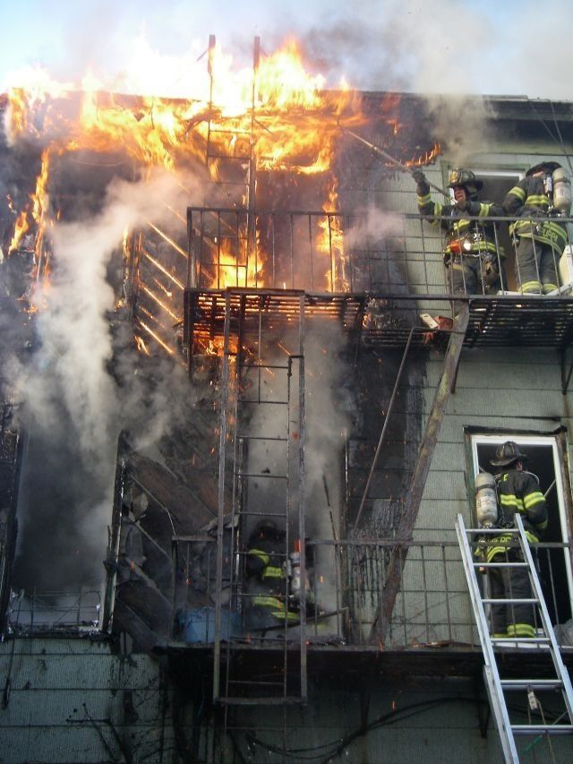 Firefighters fighting back a blazing fire from an upper story. They do this because they want to and are built that way. Thank you, firefighters for all thay you do!