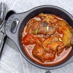 Traditional South African potjiekos - beef & BBQ sauce stew cooked outdoors in a cast-iron pot