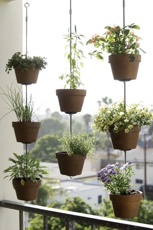 Make a DIY vertical garden that easily fits in an apartment balcony or small backyard! This space saving garden uses ropes, a few cuts of wood and clay garden pots to display and hang flowers, herb or vegetables. We give you directions to make this DIY outdoors project and suggest plants to pot in the clay containers.