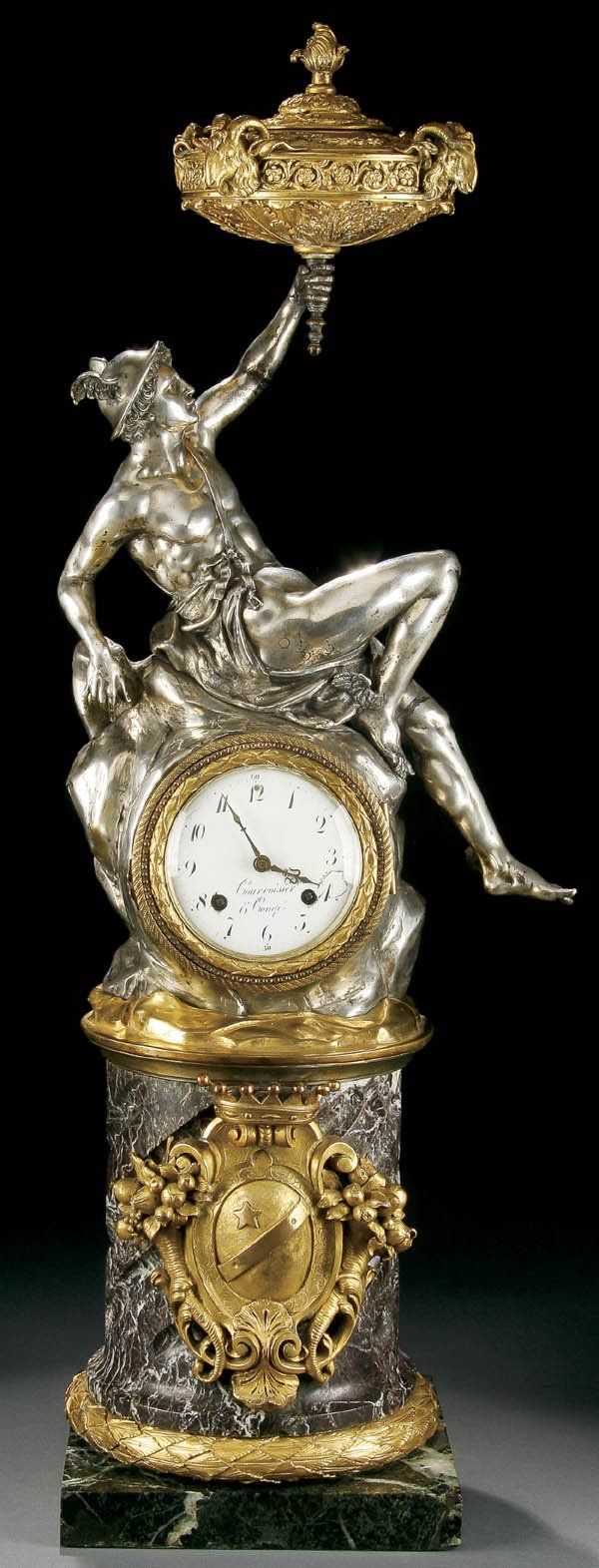 "French neoclassical figural clock, mid 19th century, ""Mercury with Torchere"", the silver plated figure of Mercury holding a gilt bronze lidded torchere with sculpted rams heads resting on a rockery peak containing a brass movement with enamelled dial."