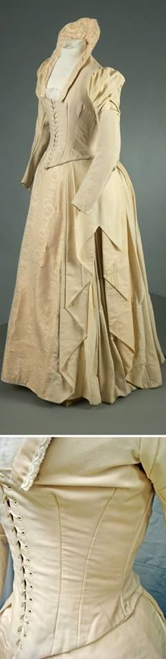 Wedding dress, cream wool blend & silk moiré w/metal supports & closures. Boned bodice, high-hip length; pointed waistline; princess seams in back; center front lacing; lining has hook & eye closures; Juliet sleeves with puffed top, then straight; square neckline w/standing collar supported w/wire. Skirt has draped box pleats on center left w/angled cascade effect; front panel of silk moiré. Attached bustle panel w/pleating at center back. Photo: Michael Nelson. Vassar College Costume…