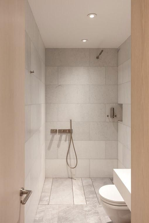 """How a Simple Bathroom Renovation Turned Into an Entire Apartment Overhaul: Night and day! The small bathroom, which originally had dark tiles, has been converted into a bright, open wet room. """"David knew he wanted a Japanese bidet toilet and the Scandinavian 'open' wet-bath,"""" Korntreger says. The slab-marble walls and floor are from ABC Stone."""