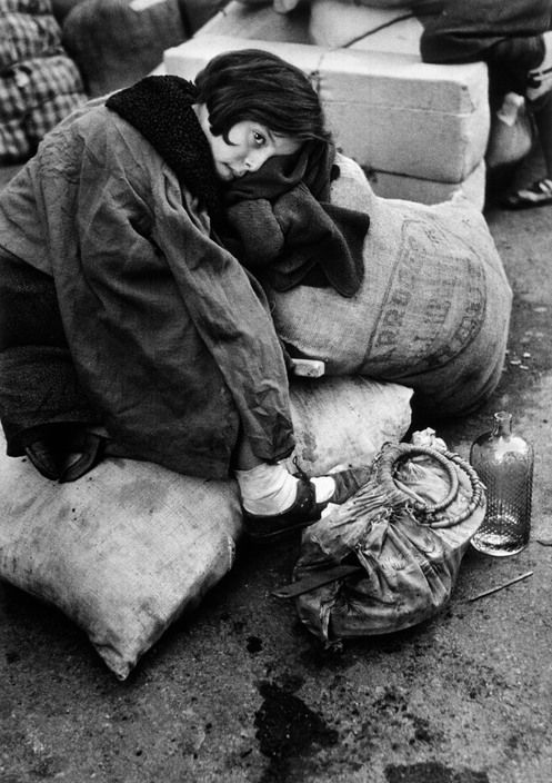 SPAIN. Barcelona. January 1939. Little girl resting during the evacuation of the city.By Robert Capa