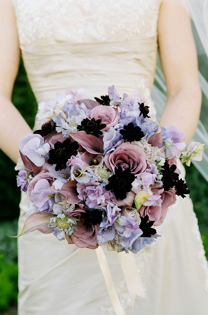 Chocolate cosmos make a statement among this purple bouquet of roses, calla lily, sweet pea and scabiosa by Lush Floral.