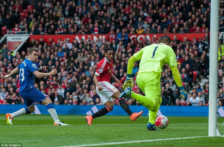Manchester United's 20-year-old star Anthony Martial (centre) slots home to score for his team past Everton goalkeeper Joel Robles
