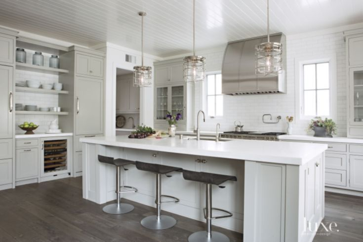 The kitchen's cabinetry includes open shelving, a built-in wine rack and a glass-front unit to display stemware. Ligne Roset barstools and pendants by Ralph Lauren Home lend a modern touch. The island's faucets are from B&C Custom Hardware and Bath.