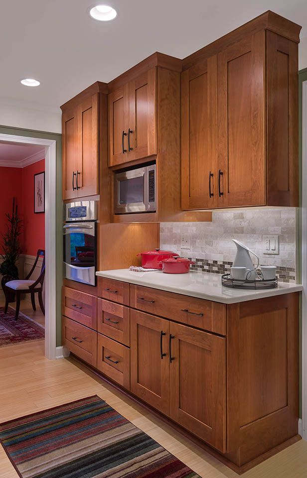 Colors microwave in cabinetry under mounted lighting for Cherry and white kitchen cabinets