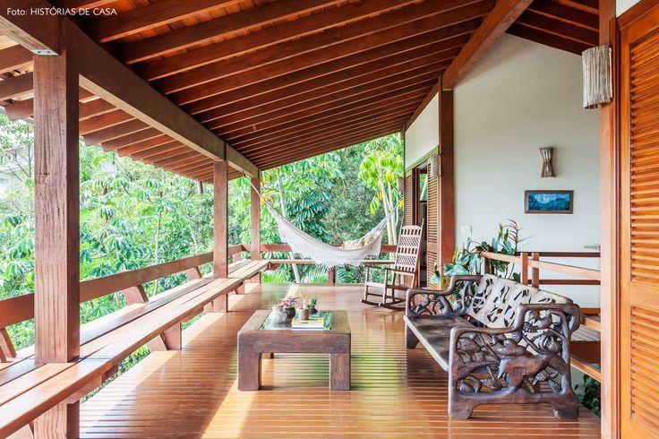 Varanda de casa de praia tem bancos estruturais de madeira, rede e móveis rústicos.