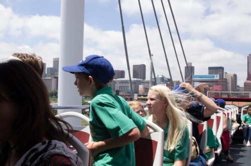 A tour bus full of students crosses the Nelson Madela Bridge. The bridge is on the route which the bus takes around Johannesburg. The kids look over the hustle and bustle of the buzz of Jozi's CBD.    The double decker open top bus gives you a perfect view across Johnnesburg's CBD.