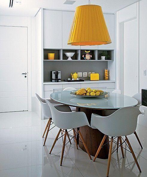 Mesa oval, de vidro, com cadeiras eames