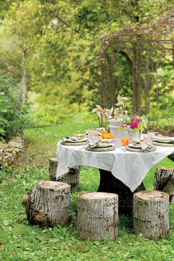 Kids' Table - Virginia Farmhouse Summer Party - Southernliving. The coolest kids' table ever uses tree stumps as fairy tale-like seating.