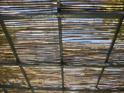 "Shade that still allows you to see the sky and the wind and heat can rise through it.  Its pretty too.   Here it is a roll of bamboo fencing.   for fabric shades see ""How to Add a Track for a Shade Cloth to a Pergola"""