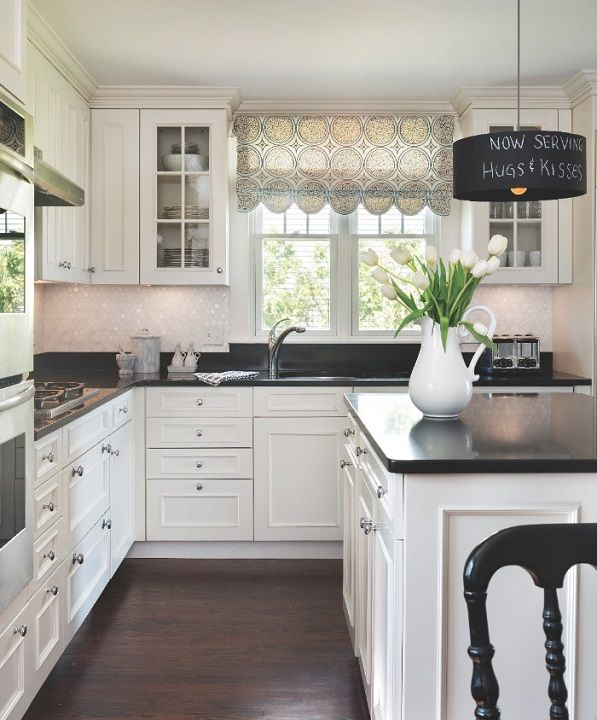 The kitchen features a mother-of-pearl backsplash and a striking black-and-white color scheme.