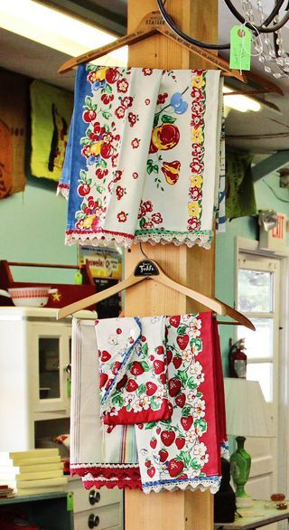 Vintage-style dish towels displayed on wooden hotel hangers.