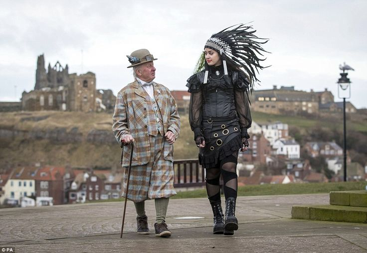 Steampunk Sophie Peech (right) walks along Whitby promenade with a man sporting checked plus fours, a bowler hat and winged goggles. The pair visited the seaside town for its first steampunk festival this weekend. Ms Peech wore a black feather headdress and a leather corset-like top with black gauze sleeves
