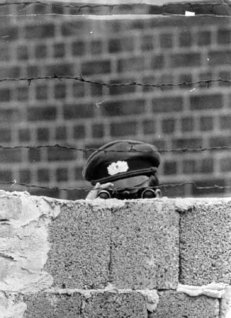 A GDR soldier keeps a watchful eye over the Berlin Wall [1960s]