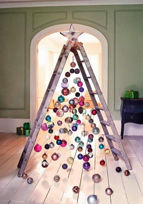 a ladder with ornaments hanging from it looks colorful and industrial 25 Coolest Christmas Tree Alternatives | ComfyDwelling.com (no sources/tutorials, but lots of inspiration) #decoratingachristmastree