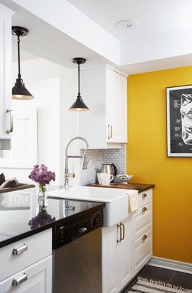 Fantastic modern kitchen with yellow accent wall, white kitchen cabinets with black polished granite countertops, farmhouse sink, slate tiles floor and black pendants.