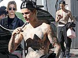 Justin Bieber shows off his tattoos as he leaves a dance studioas Hailey arrives to lunch