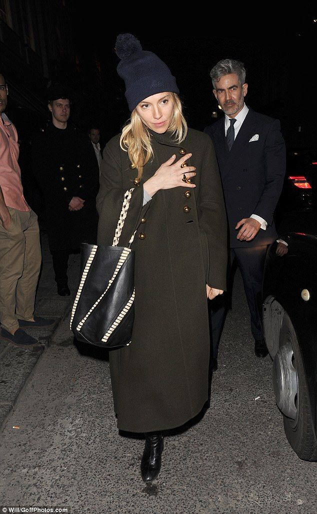Chic: Sienna Miller covered up her svelte figure in an oversized khaki coat as she attende...