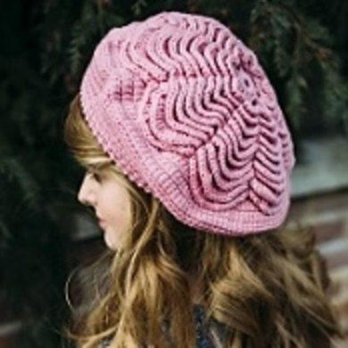 This lovely beret combines the traditional Irish Rose motif with a stylish, contemporary design.Made in one piece from the centre outwards, rounds of petals are built up to create this stunning beret.The design uses linked treble (US: linked double) stitches to form a sturdy fabric that will keep its shape.  The pattern includes instructions on how to work a linked treble stitch, and there are photographs to help too.Roisin (pronounced Ro – sheen), means 'little rose', and is an apt name for…