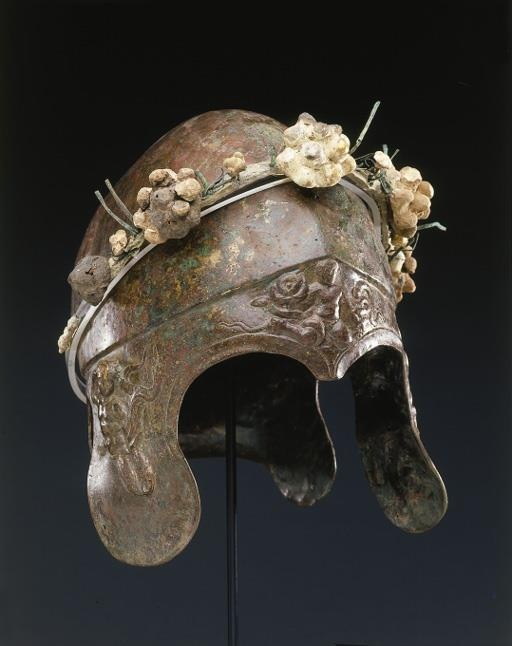 A GREEK BRONZE CHALCIDIAN HELMET circa 4th century b.c. Of hammered sheet, with a rounded bowl off-set from the neck- and cheek-guards and the brim by a ridge, the neck-guard flaring along the back edge, the forward elements adorned with relief ornament illustrating the Herakles cycle, including, on the brim, the infant Herakles struggling with the serpents of Hera, on the left cheek-guard, the hero wearing the Nemean lion skin, battling the Lernean Hydra