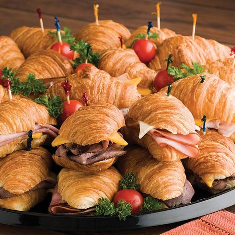 Snack-Lits: Mini croissant rolls are filled with smoked turkey breast, honey ham, roast beef and baby Swiss and yellow American cheeses. Cherry tomatoes and green olives accent the tray.