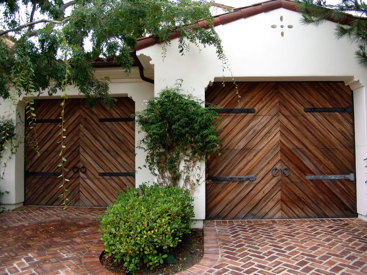 These custom made Spanish style garage doors feature a beautiful herringbone pattern and feature long hinged decorative hardware. The doors are made of Clear cedar and are distressed with a wire brush to give off an aged look. contact us at zieglerdoorsinc.com with any questions regarding a custom built garage door or gate.