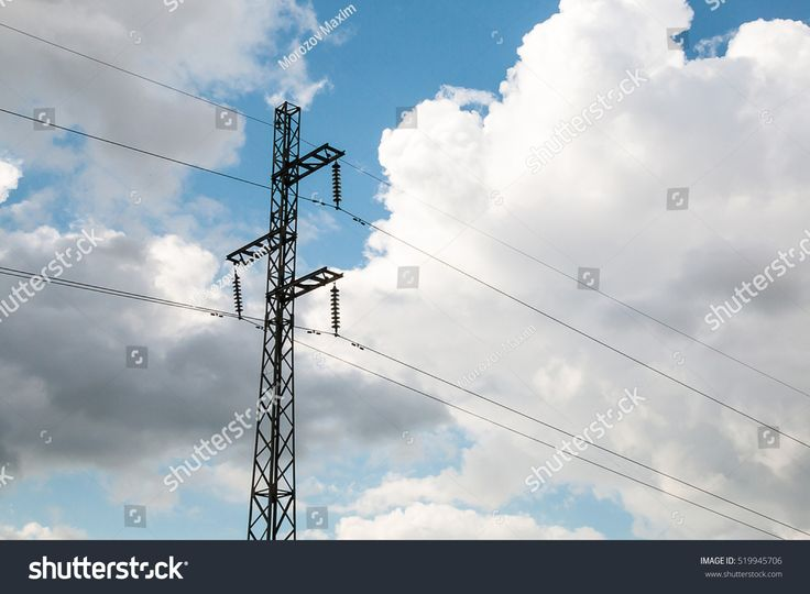 Electric pole with wires on a background of blue sky with white cumulus clouds.