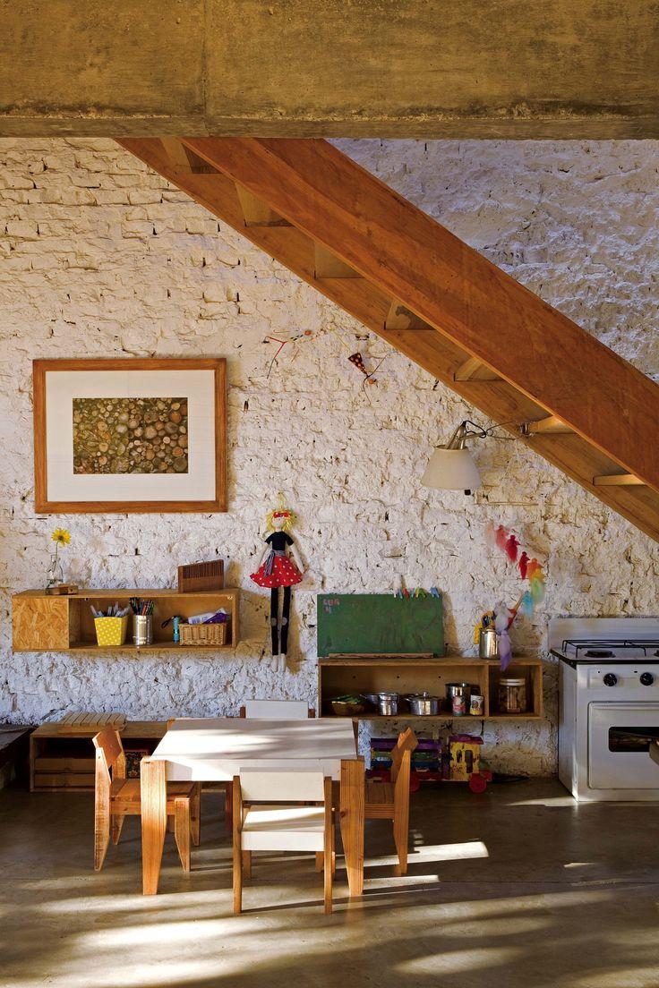 Rincón de juego con muebles y juguetes de madera debajo de una escalera en una casa sustentable de Beccar, obra de AB Estudio. Foto: Javier Csecs