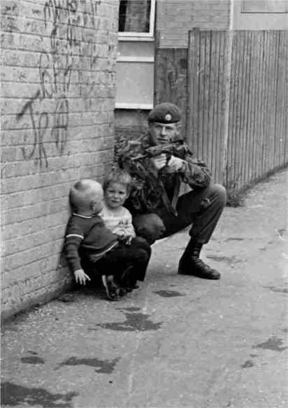 British soldier uses two small children as cover while on patrol in Belfast, Northern Ireland during the 1970s (412x583)
