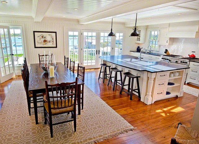 Kitchen island with sink , storage and sitting area all opened up into additional living area. Love the lighting over the bar and floors.