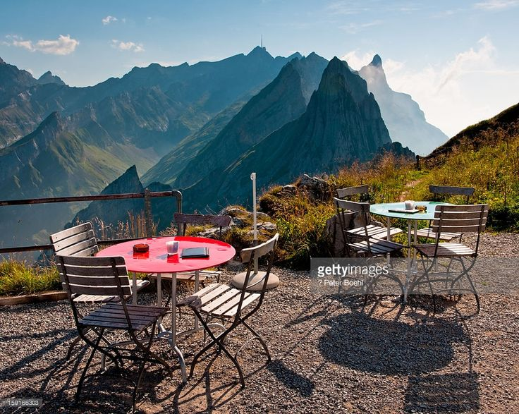 Terrace of the restaurant Schäfler, view towards Säntis, two tables and a few chairs, blue sky. Appenzellerland.