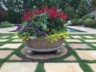 Brookfield's Fairfield Bowl Planter elevated on four Scroll Feet make a stunning focal point near the pool!