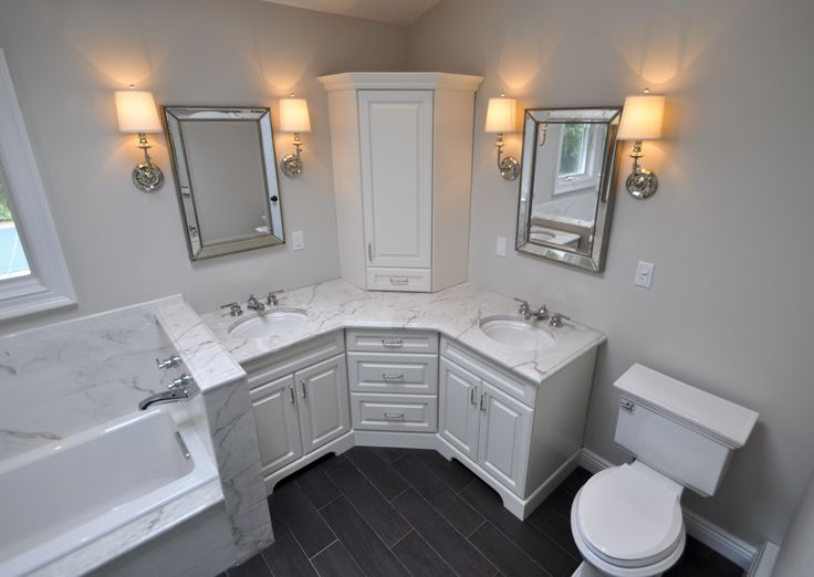 Custom Master Bathroom, with double corner vanity, tower cabinet, wall sconces, toilet and built in tub area.