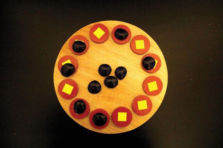 """Le jeu traditionnel targui est joué par les touaregs du désert. C'est un jeu solitaire qui consiste à manger tous les pions et n'en laisser qu'un, par un principe de """"saute mouton"""". Jeu africain"""