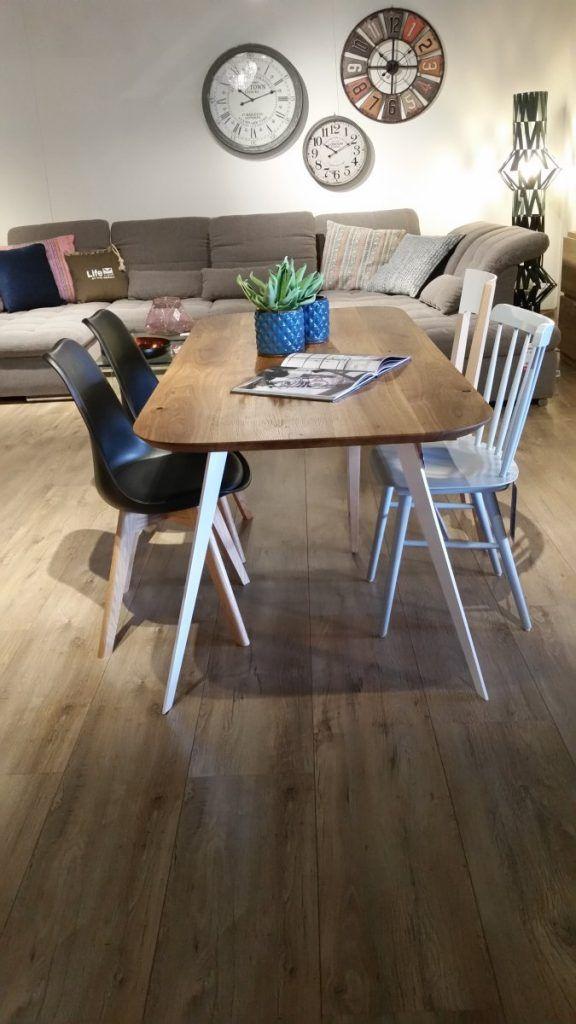 Nowoczesny stół sprawiający wrażenie unoszącego się nad ziemią. Stół o cienkim drewnianym blacie w naturalnym kolorze i białych nóżkach. Krzesła w 2 stylach: białe, klasyczne krzesła w stylu PRL-u oraz nowoczesne krzesła o plastikowym siedzisku i drewnianych nóżkach.