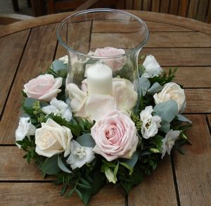 Wedding Flowers A hurricane lamp at the center of this ring of beautiful roses and foliage means that the arrangement would be perfect for both daytime and evening. (Don't forget to check that your venue is willing to let you use candles)