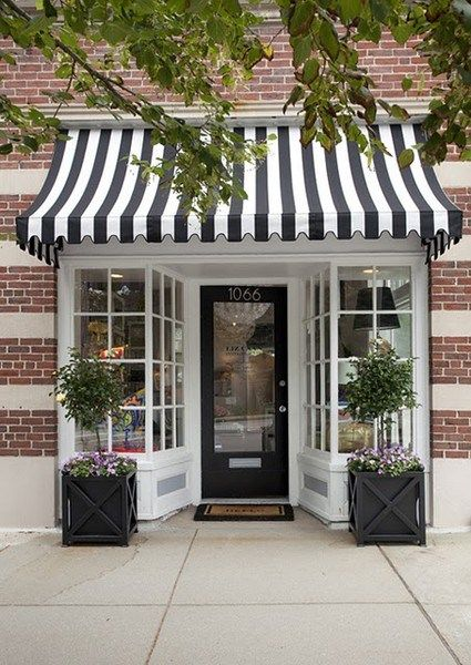 Inviting boutique storefront, adorable black and white awning with simple topiaries, slightly vintage but still modern design.