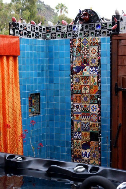Outdoor shower with blue, black, gray and Mexican mosaic tiles. Orange shower curtain. Pig shaped shower head