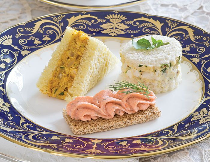 Clockwise, from upper left, Coronation Chicken Salad, Watercress and Egg Salad Tea Sandiches, and Dilled Salmon Mousse Canapés from our Fit for a Queen Tea.